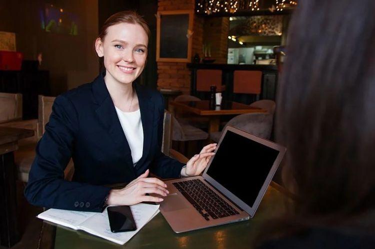 mulher executiva sorrindo com notebook na mesa