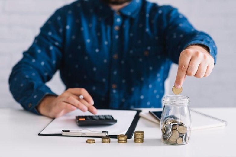 homem calculando colocando moedas no pote de vidro
