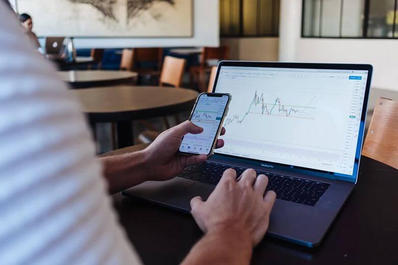 pessoa mexendo no celular e notebook com gráficos