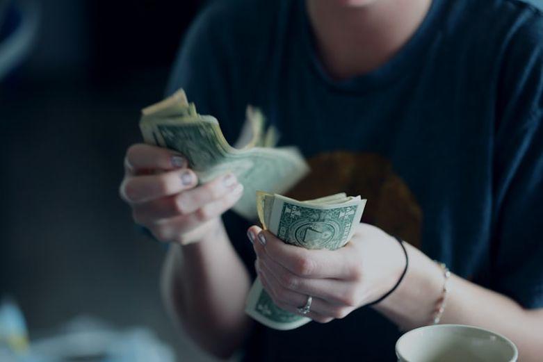 pessoa contando notas de dolares