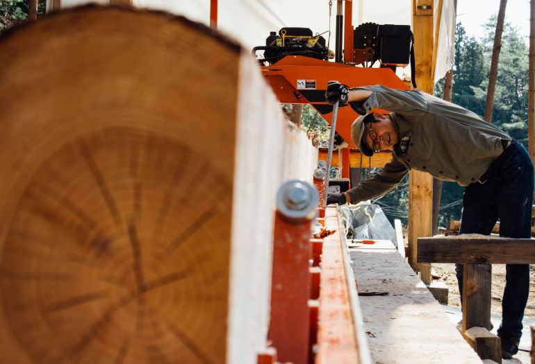 Woodworker Tak Yoshino turning a log on LT15 sawmill