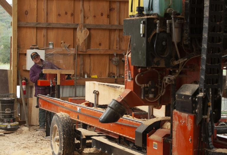 Megan sawing lumber on Wood-Mizer LT70 Wide sawmill