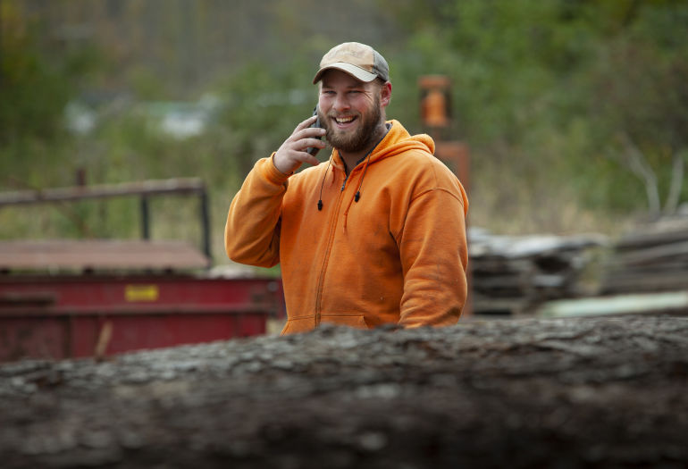 Luke of Holland Timber Company speaking on the phone smiling