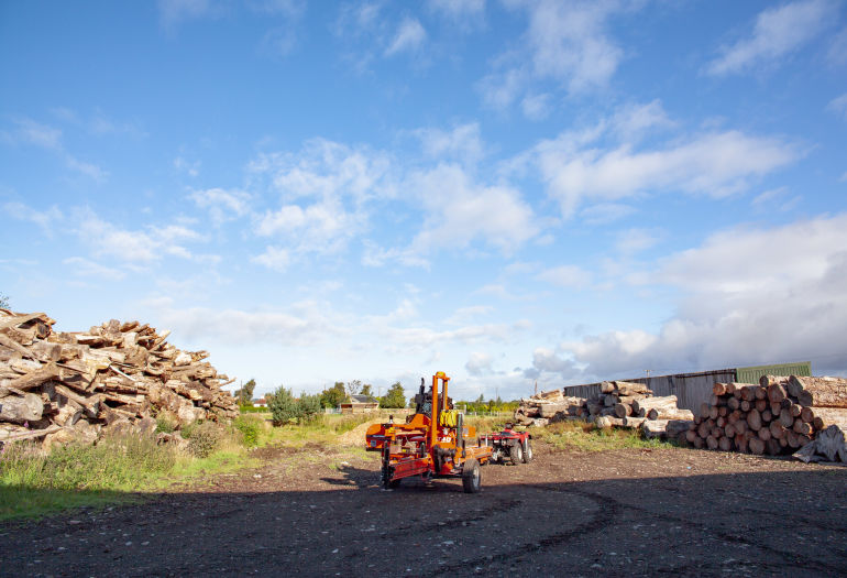Landscape view of outdoor space with log piles and LT40 Portable Sawmill