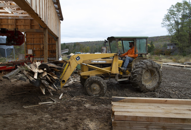 Luke moving log scraps at Holland Timber Company worksite