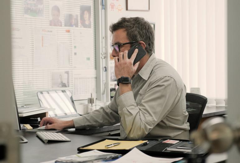 Adolfo Jr speaking on phone at desk