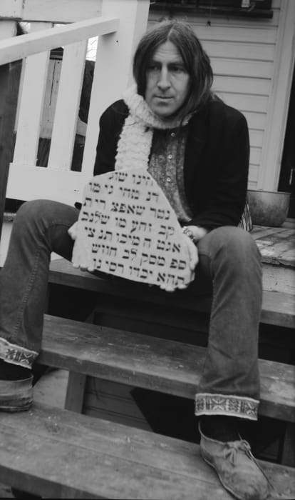 Wallace Berman, seated with stone, Topanga by George Herms
