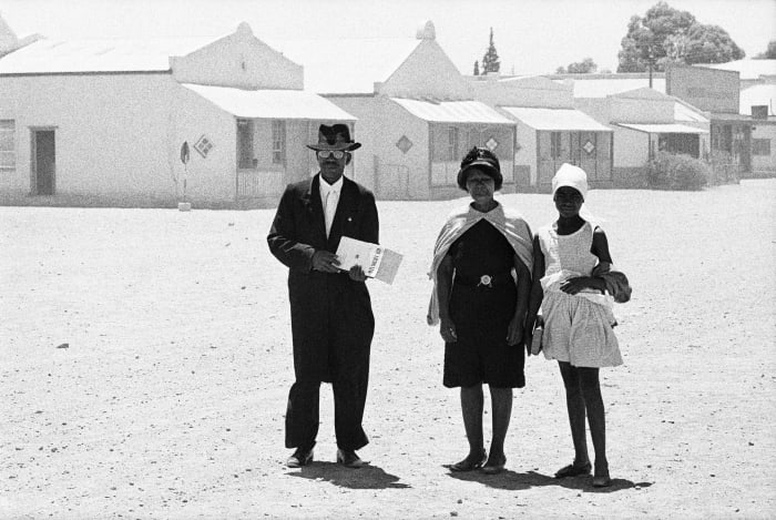 An elder of the Dutch Reformed Church walking home with his family after the Sunday service, Carnavon, Cape Province (Northern Cape), January 1968 by David Goldblatt