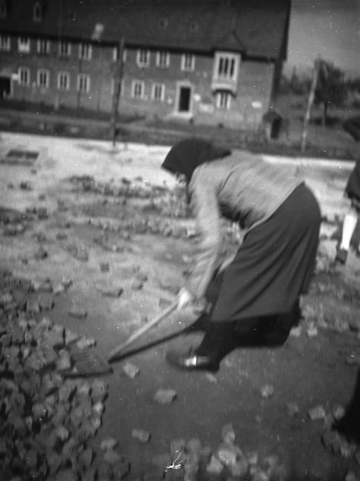 A German woman is cleaning leftovers of where her house was before it was destroyed by bombs. Kassel, 1947 by Jonas Mekas