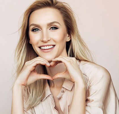 After visiting the houston dentist, women wear a beautiful smile with a heart sign