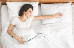 Depressed young woman lying in bed and feeling lost