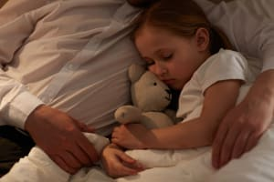 child with nightmares sleeping in her father arms