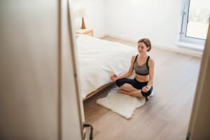 A young woman doing yoga exercise in morning in a bedroom