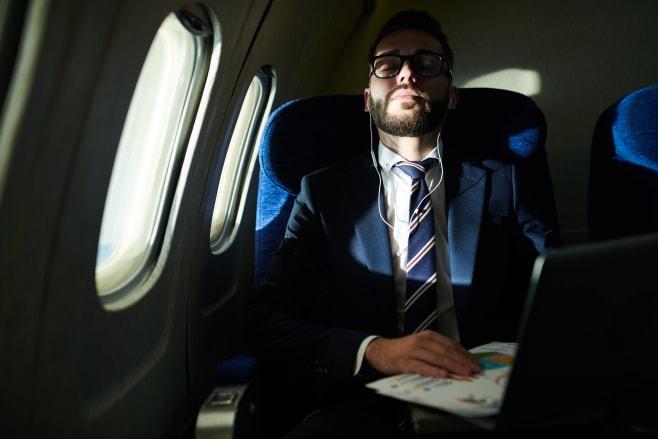 Portrait of successful businessman sleeping during long flight in dimly lit plane