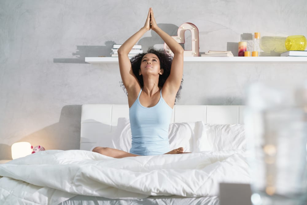 Young woman doing yoga in bed