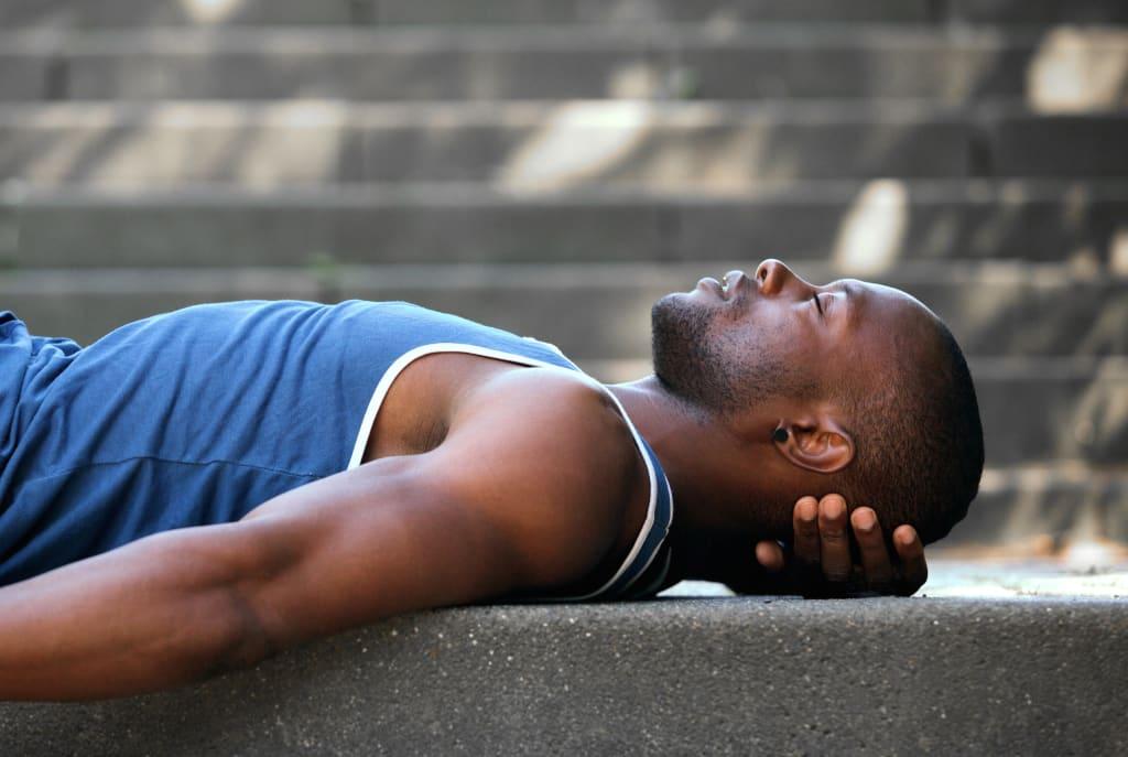 Side portrait of a man sleeping outside