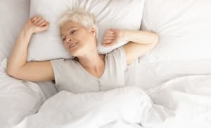 Senior woman lying down in her bed at home