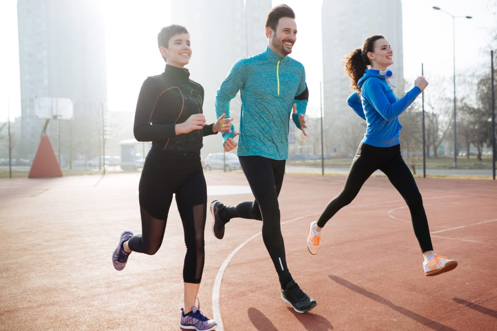 Happy friends exercising by running together outdoors living active healthy lifestyle