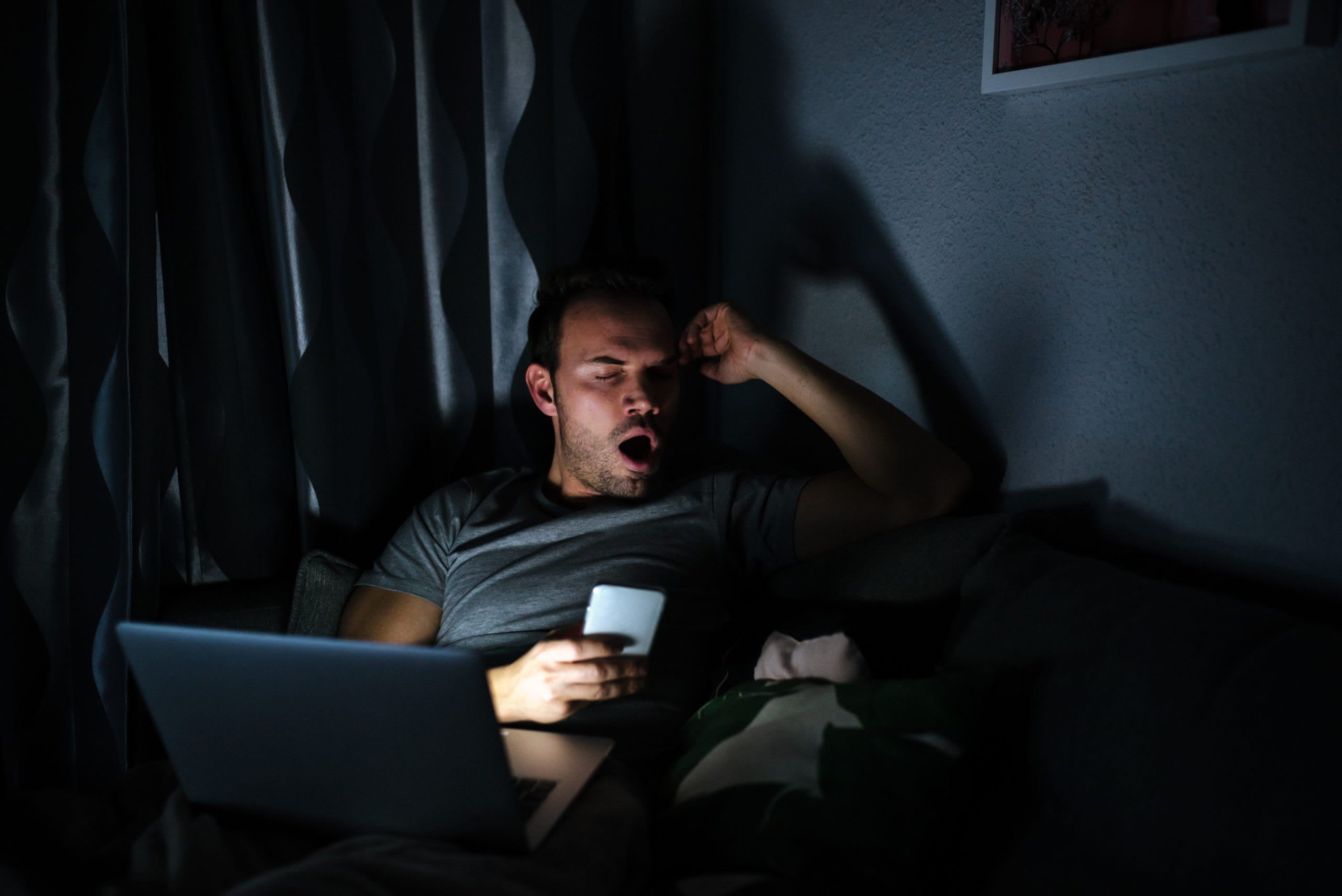 Man sitting with a phone screen and computer getting tired