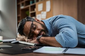 man with narcolepsy sleeping at the office