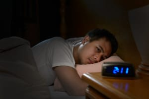 Depressed man suffering from anxiety lying in bed