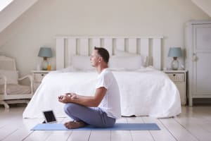 Man Meditating in front of bed