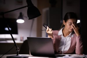 Young businesswoman touching her head while sitting at her workplace with laptop she tired of her work at office