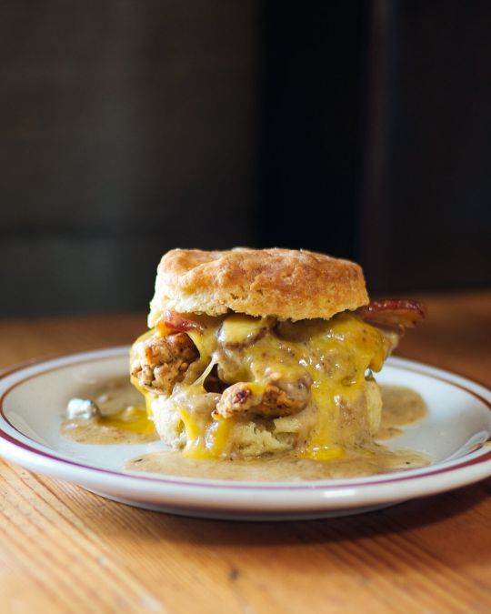 Pine State Biscuits\' Reggie Deluxe is stacked high with buttermilk-fried chicken, a fried egg, cheddar, bacon and sausage gravy.