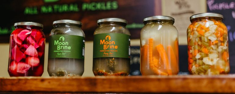 A row of jars of fermented vegetables (including carrots, pickles and beets) from the Portland pickle brand MoonBrine.