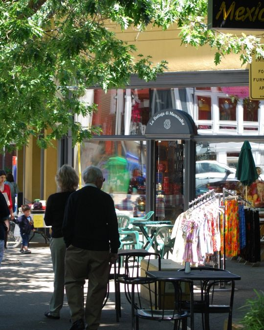 tables and shop items displayed on the sidewalk as people walk by on NW 23rd Avenue