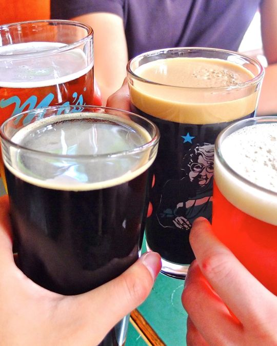 Four hands with four beers toast to world-class beer and spirits at Rogue Distillery and Public House.