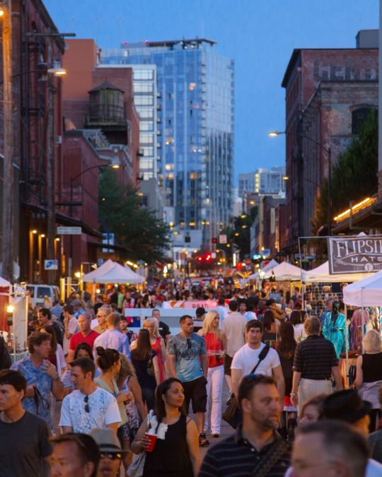 a twilight street filled with people browsing tents with items on display