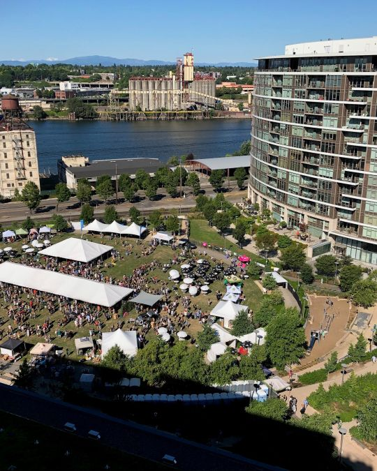 Aerial shot of an urban riverside park with festival tents and umbrellas