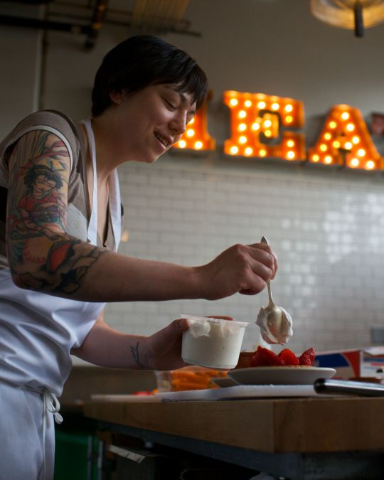 """A chef tops a strawberry dessert with whipped cream in front of a neon sign reading \""""MEAT\"""""""