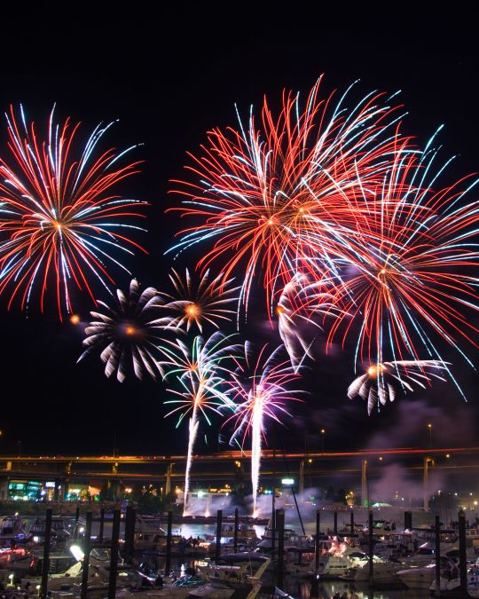 Fireworks burst in a night sky above a river, with boats in the foreground and a bridge in the background