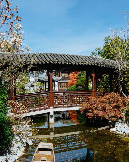 covered bridge crossing a narrow garden stream