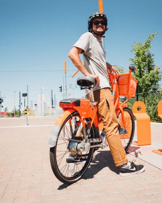 A person standing over an orange bike next to bike stands