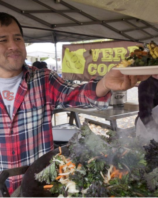 """man in an outdoor market handing a plate of food to a customer in front of a sign reading \""""Verde Cocina\"""""""