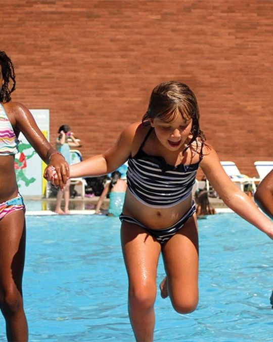 three children holding hands in a pool