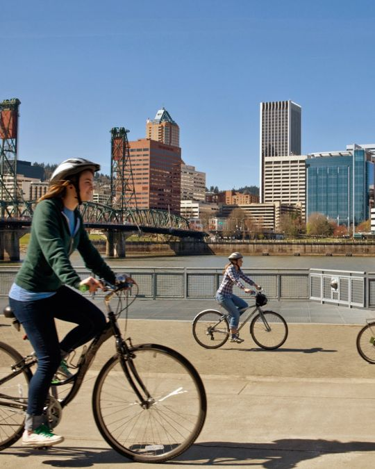 bikers riding along the east bank of the Willamette river with the Hawthorne bridge and Portland downtown buildings in background