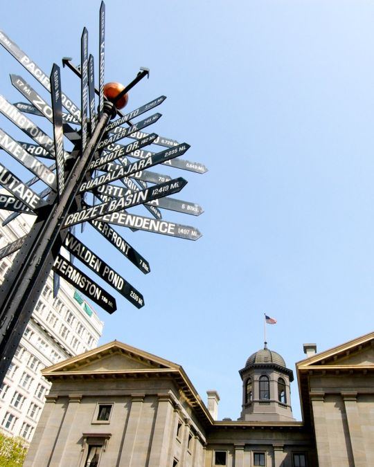 A sign post with dozen of city names in front of a historic building
