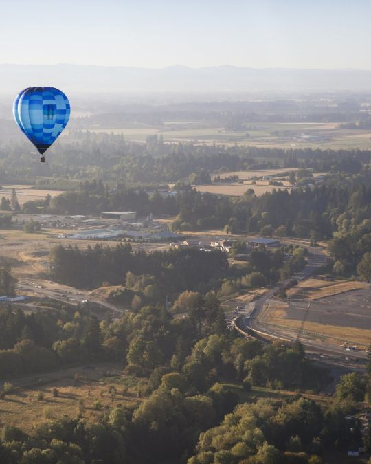 A hot air balloon floats above a wooded valley.