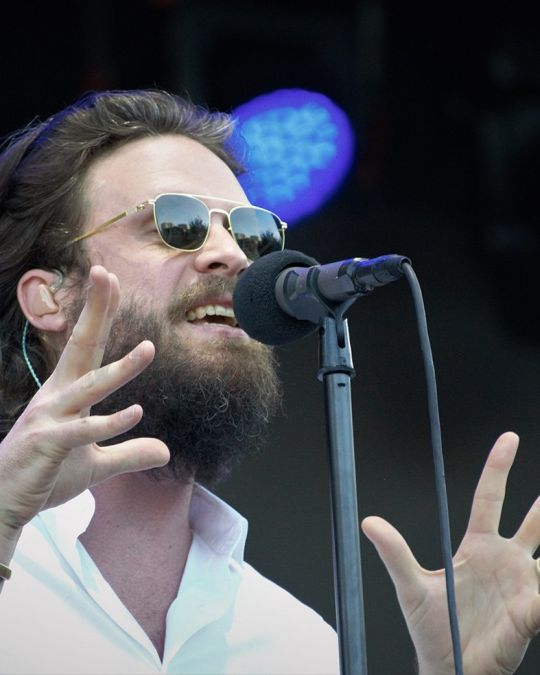 a bearded singer wearing sunglasses emotes into a microphone
