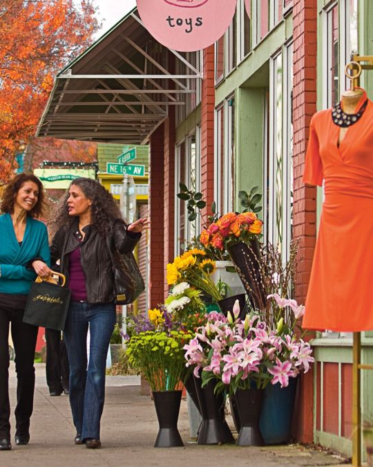 Two shoppers walking down the sidewalk in front of shops displaying flowers and clothing on Northeast Alberta Street