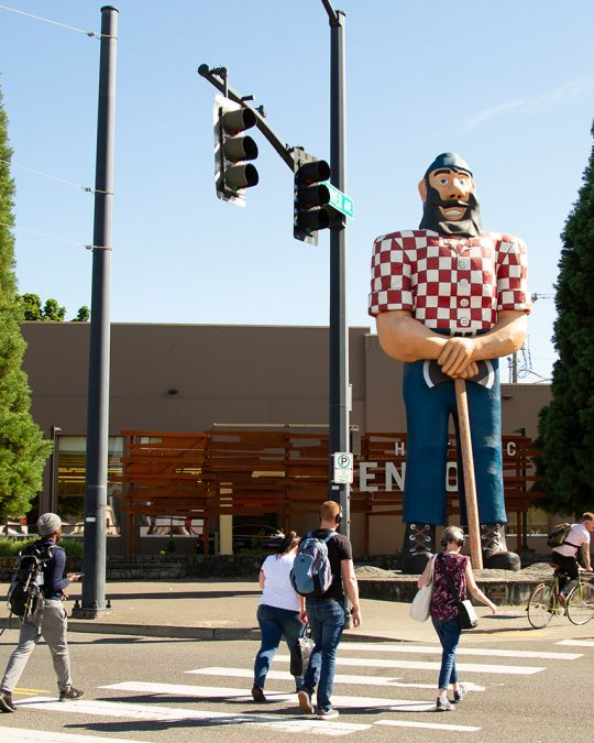 People cross the street in front of a 31 foot tall statue of Paul Bunyan