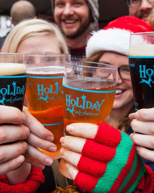 four beer drinkers wearing hats and gloves clink glasses