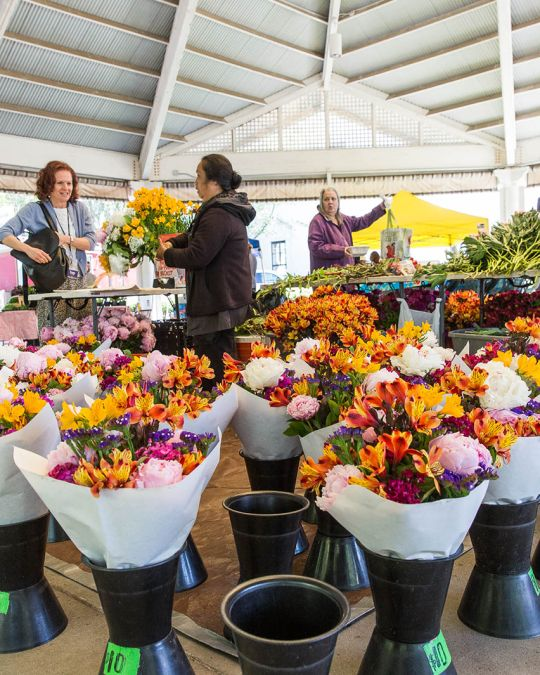 flower vendor standing in the middle of many colorful bouquets selling a single bouquet to a customer at a farmers market