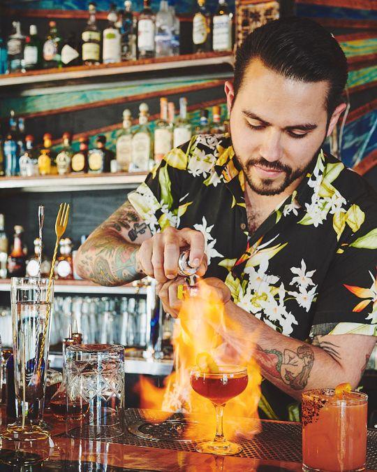 a tattooed bartender in a Hawaiian shirt sets a cocktail on fire