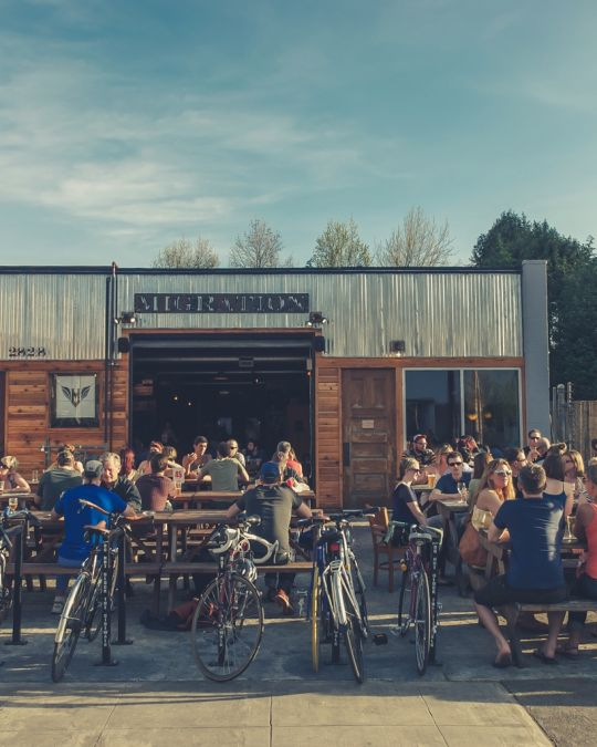 people sitting and drinking at brewery patio