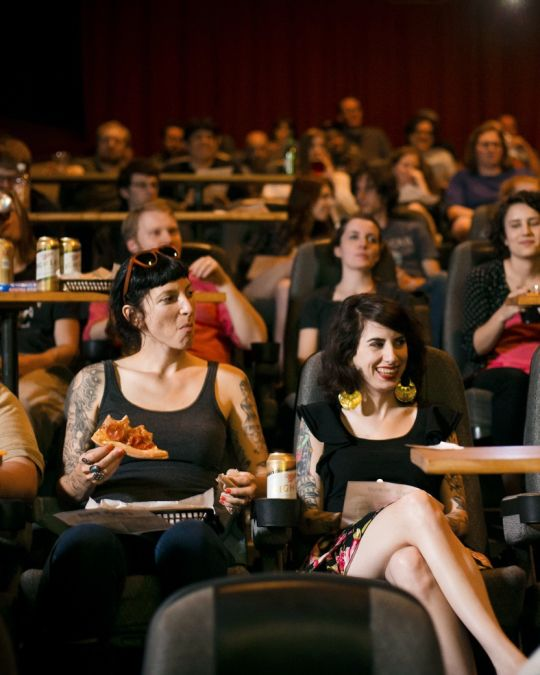 movie goers enjoy pizza and beer